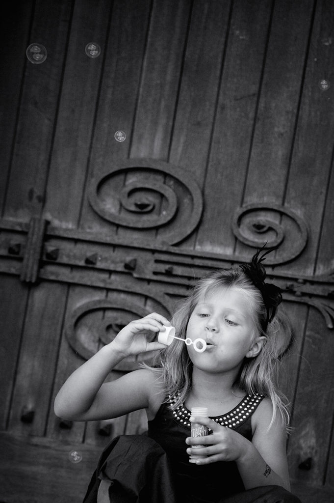 little girl blowing bubbles after the wedding ceremony